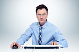 Man with glasses and tie at the keyboard in front of computer
