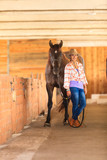 Cowgirl standing next to brown horse friend - 132054058