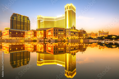 Spectacular golden skyline of Macau in China, reflected in the water at twilight плакат
