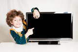 Cute kinky prince embracing television, he points his index finger on a blank screen. Gray background.