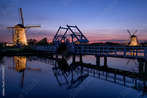 Plakat Illuminated windmills, a bridge and a canal at sunset