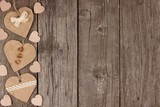 Side border of handmade burlap hearts with ribbon and buttons over a rustic wooden background