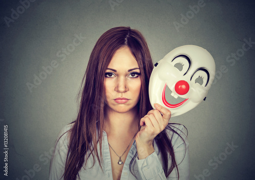 Upset worried woman with sad expression taking off clown mask Poster