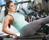 Pretty woman working her core muscles in the gym