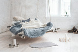 Fototapety White loft interior in classic scandinavian style. Hanging bed suspended from the ceiling. Cozy large folded gray plaid, giant knit blanket, super chunky yarn, arm knitting. Trendy room design.
