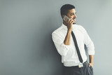 Handsome young black man with mobile phone in the office
