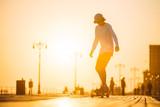 Sylwetka młodego chłopca jazda longboard na deptaku, czas letni zachód słońca