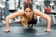 Young beautiful woman doin pushups in the gym.