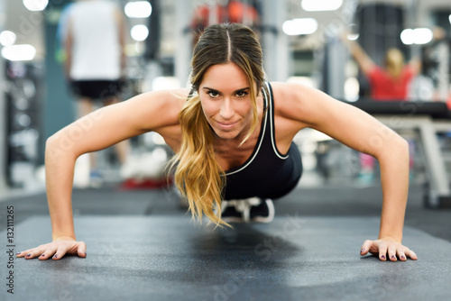 Young beautiful woman doin pushups in the gym.