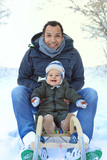 Father and baby on a sled - family having fun in winter