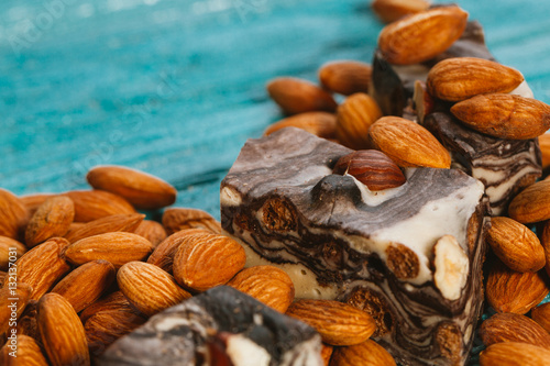 Póster candy paste and almonds on blue wooden background