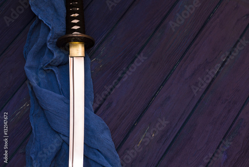 Poster japan katana sword on the wood background with the blue shawl