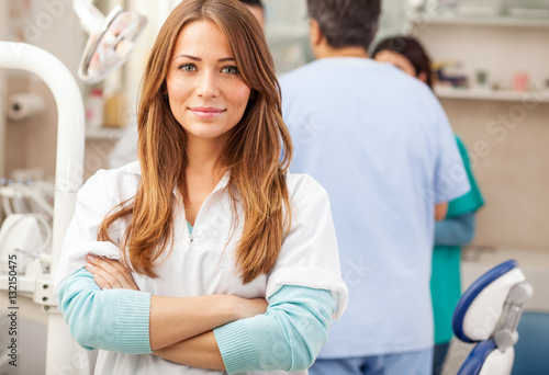 Fototapeta Young blond hair female dentist standing in his office and looking at camera.