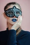 Young beautiful woman with black venetian mask