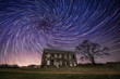 Vortex spiral star trail behind an abandoned home