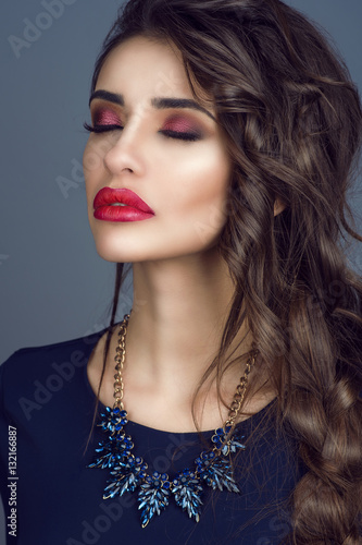 Poster Portrait of gorgeous young lady with perfect skin, red filled lips and long plaited dark hair standing with closed eyes