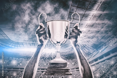 Composite image of cropped hand of athlete holding trophy 3d