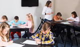Elementary age children drawing at class in school