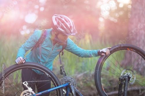 Poster Female biker repairing mountain bike