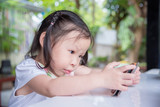 Little asian girl playing game on cellphone