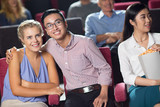 Happy young couple watching new movie in cinema