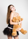 sexy young woman in very little black dress holding a teddy bear