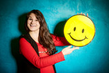 woman in a red blouse and black jacket standing against the backdrop of a blue wall and holding a big yellow smiley