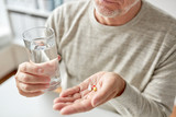 close up of old man hands with pills and water