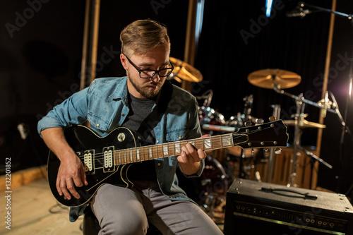 Poster man playing guitar at studio rehearsal