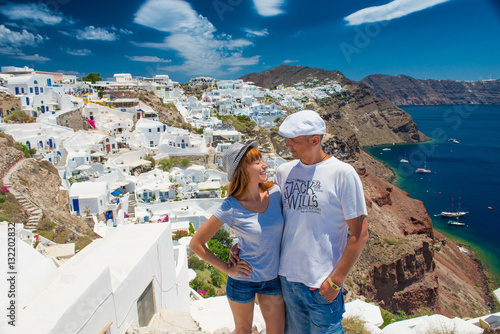 Couple on  island of Santorini. Cheerful couple travels to the islands of Greece, the most romantic island on earth - Santorini. concept of family tourism and travel, spirit of freedom and positive