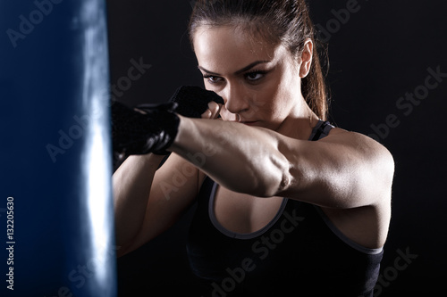 Póster Studio shot of female boxer punching a boxing bag.