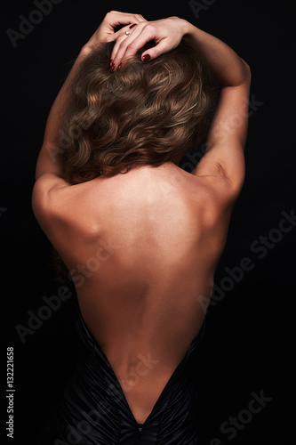 beautiful back of young woman in a black sexy dress.beauty brunette Girl with curly healthy hair