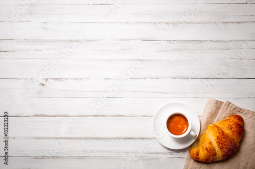 Poster cup of espresso coffee with croissant on white wooden table, empty space on top