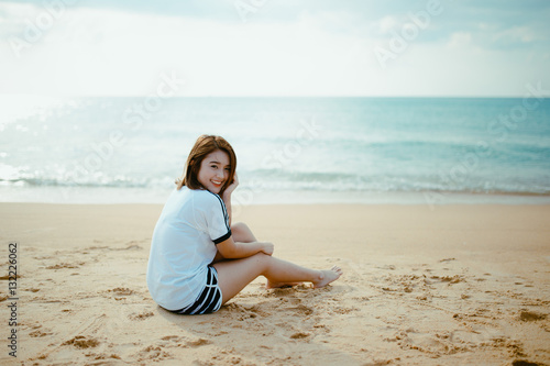 Poster Bueatiful girl sit on the beach.