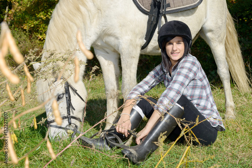 Portrait of a pretty young woman with white horse riding
