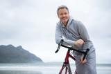 Portrait of happy man leaning on bicycle at beach