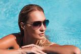 Красивая девушка загорает в бассейне