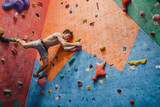 Male sportsman climber before jump on artificial climbing wall