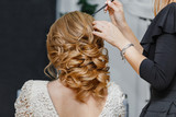 Fototapety Young bride getting her hair done before wedding by professional hair stylist