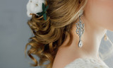 Detail of young woman wearing beautiful luxury earring and hairstyle with copy space