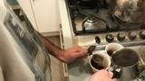 Male filters freshly brewed coffee in the kitchen