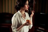 Young woman with cigar and glass of whiskey in retro atmosphere.