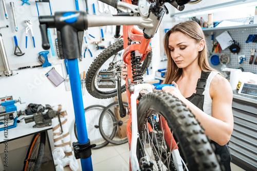 Deurstickers Watchful female worker repairing bicycle in the garage
