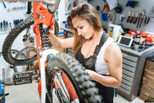 Deurstickers Persevering female master repairing the mountain bicycle