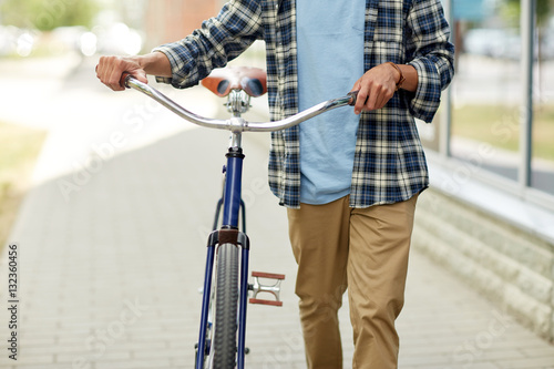 Poster close up of man with bicycle walking along city
