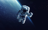 Astronaut at spacewalk. Cosmic art, science fiction wallpaper. Beauty of deep space. Billions of galaxies in the universe. Elements of this image furnished by NASA - Fine Art prints