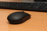 Wireless black stylish computer mouse lying on table.