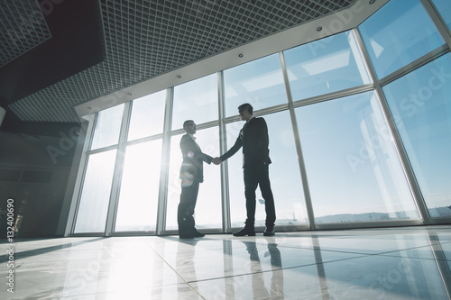Fototapeta Two young businessmen are shaking hands with each other standing against panoramic windows.
