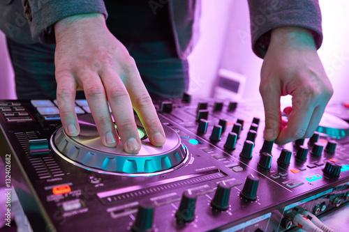 Poster DJ plays and mix music on digital midi mixer controller.