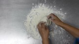 Woman baker hands kneading the dough on metal table with flour powder